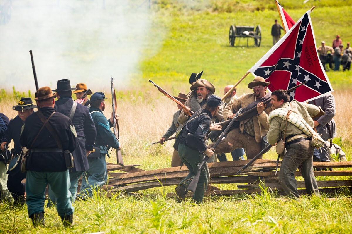 Civil War reenactors recount Confederate troops leaping a fence in an attack upon a Union force