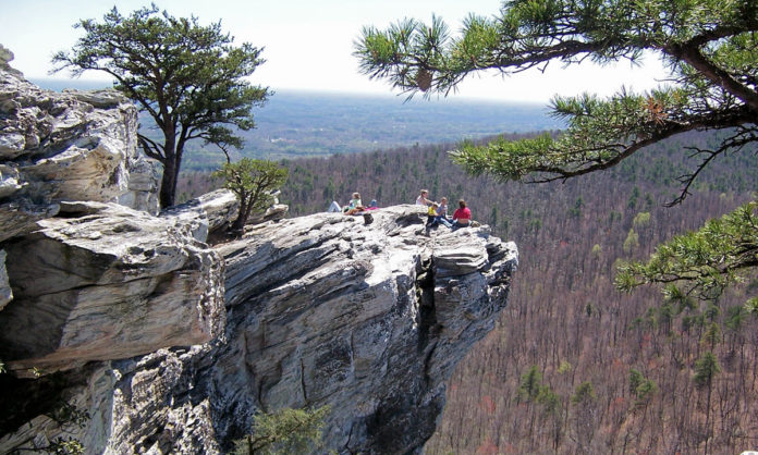 Intrepid hikers perched on a rock outcropping at Hanging Rock State Park