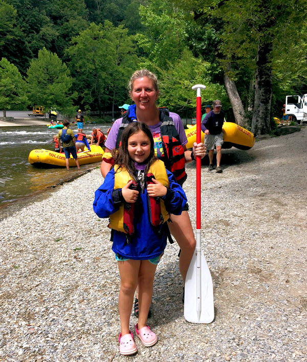 A mother and daughter stand on the bank of the Nantahala after rafting
